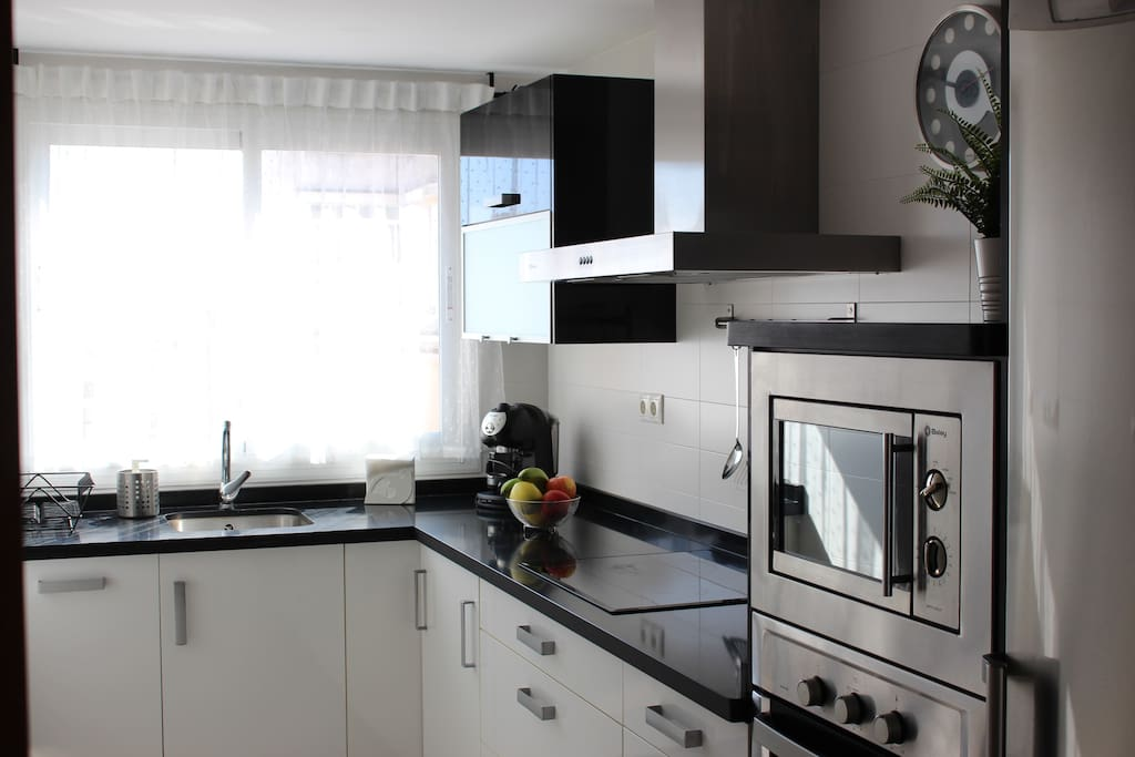 Cocina de granito blanca y negra con horno y microondas en mueble empotrado y nevera grande con frigorífico.