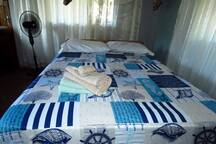 Sunrise Cottage: Bedroom 1 with double bed with shared shower + toilet, kitchen and veranda.