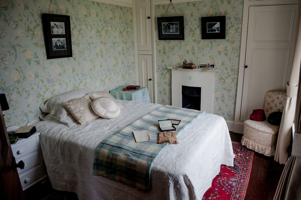 Bedroom with double bed, original fire place, wooden floors and Persian rug.
