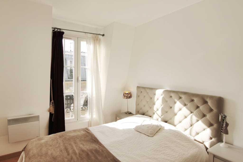 Bedroom with large double bed and cupboard