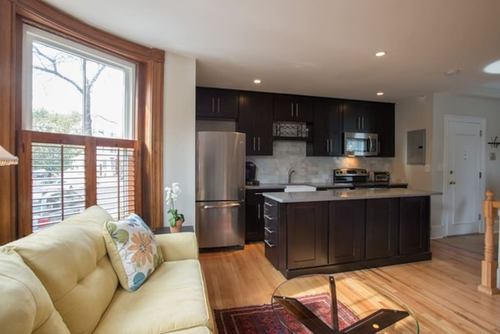 Fully equipped kitchen, gleaming hardwood floors.