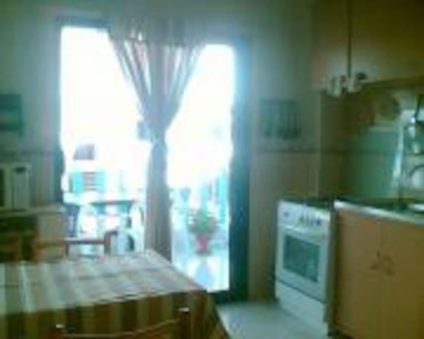 Cuisine equipee cuisiniere micro onde frigidaire ouverte sur une belle terasse avec table chaises pour prendre repas environnement fleuri.....