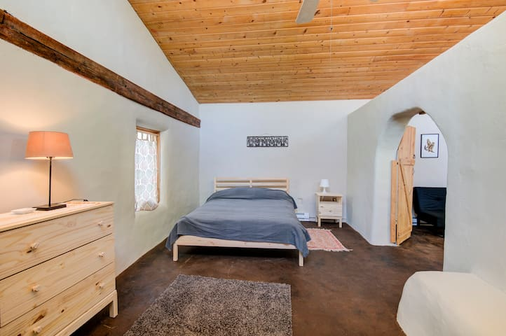 Queen bed and fold out futon couch. High wood ceilings and an adobe floor make this room eco-special.