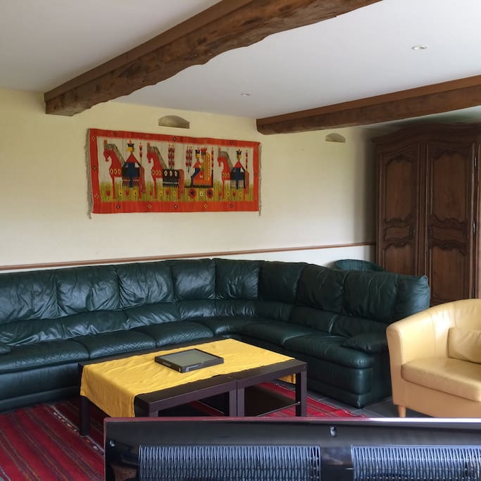 Coin salon canapé d'angle en cuir près de la cheminée