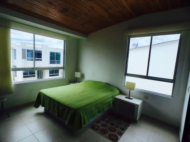 Alcoba principal con cama doble, mesas de noche con lamparas, aire acondicionado, baño privado, closet amplio y TV.