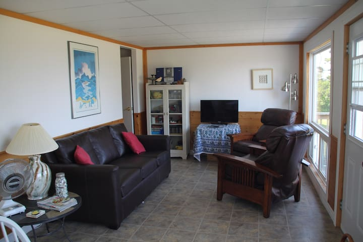 Living room with queen leather sofa bed plus two leather recliners, overlooking the sea.