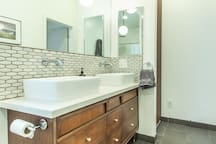 Renovated master bath with subway tile and refinished mid-century vanity