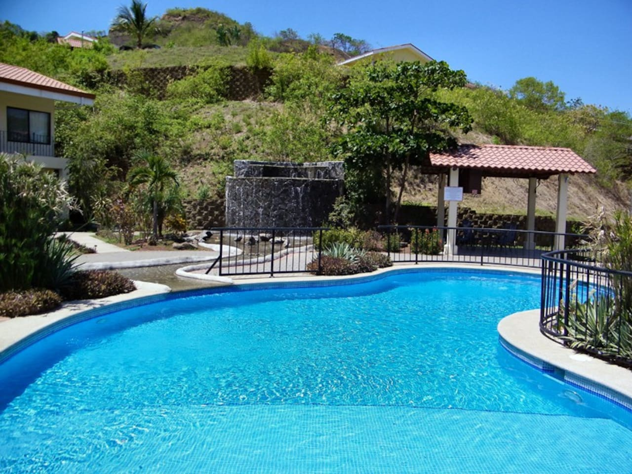 Beautifully maintained grounds with waterfall and well kept pool.