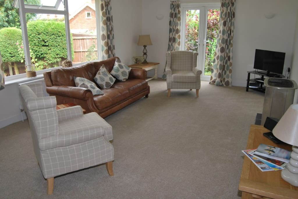 Luxury comfortable sitting room with French doors to garden.