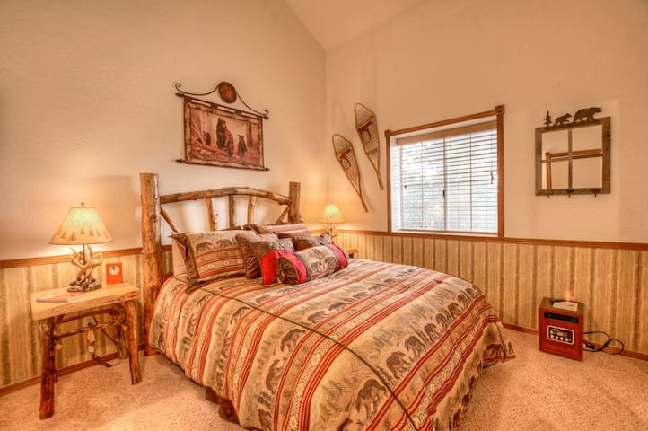 Bedroom one with queen bed and vaulted ceilings.