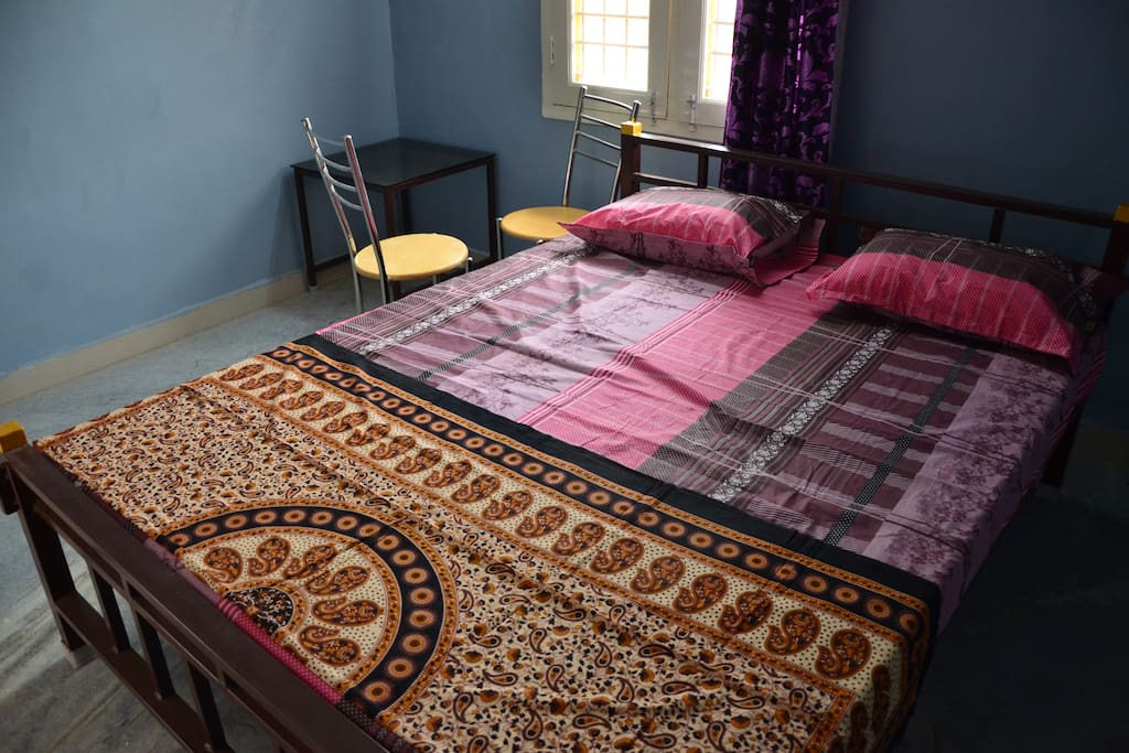 Bedroom consists of a Double bed, a fan and two chairs
