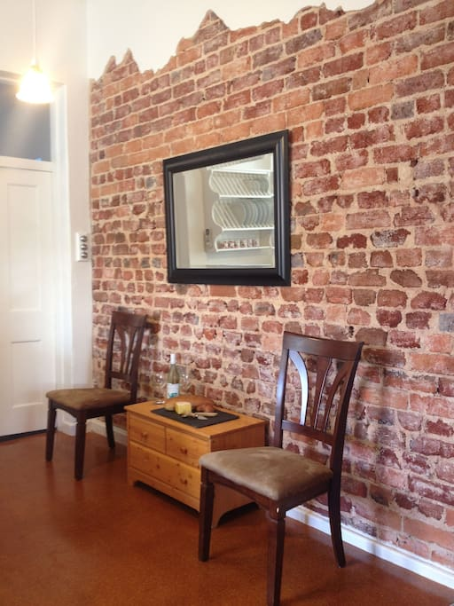 Chiseled feature wall exposes 100+ year old brick adding character to this remodeled kitchen.