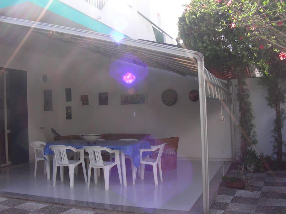 veranda attrezzata  con salotto , tavolo e sedie