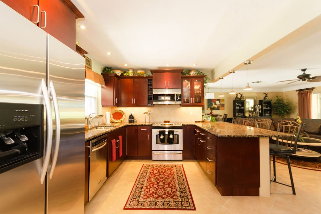 Modern kitchen with stainless appliances, granite, and eat in bar seating for 4