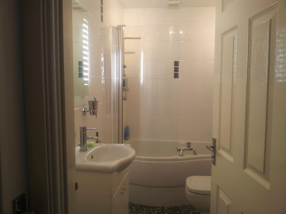 Compact modern heated bathroom with curved bath & overhead shower