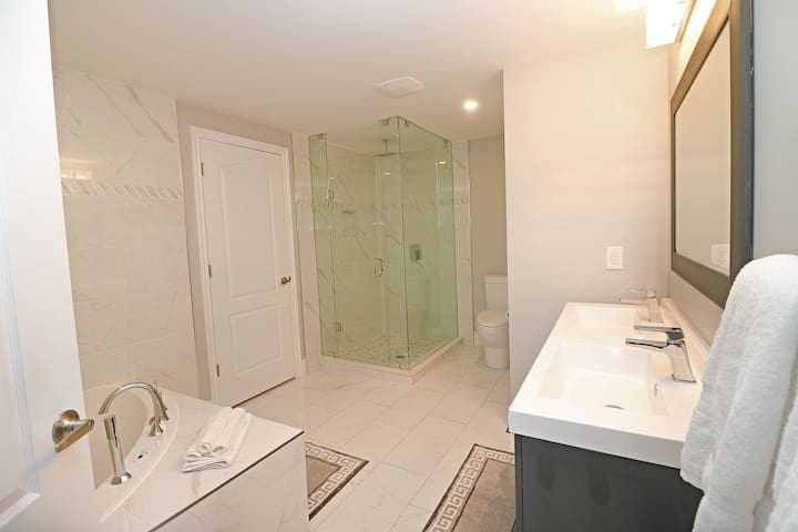 Modern and spacious, 4-piece bathroom with jacuzzi and rainfall shower.