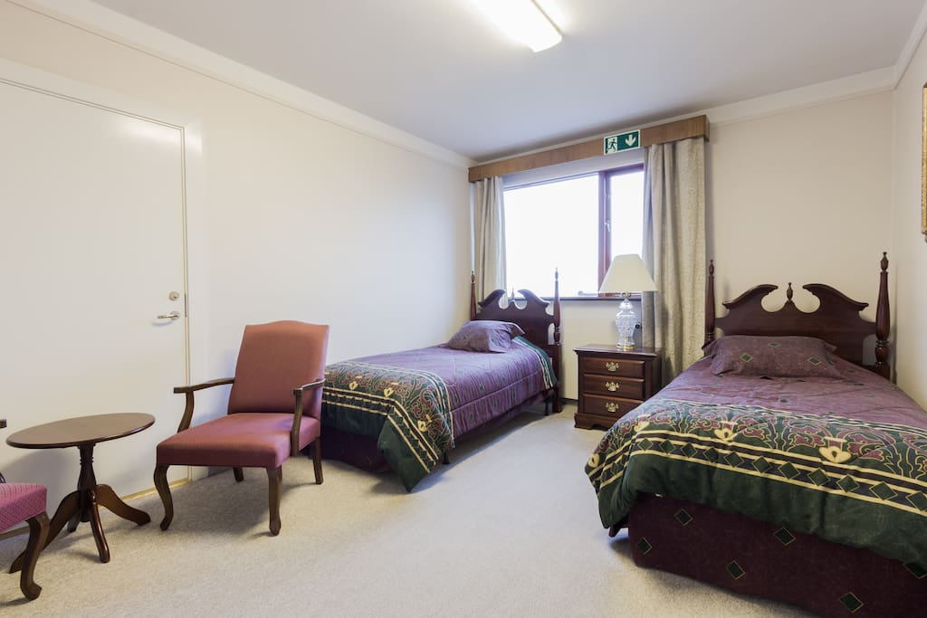 Private room with two comfortable single beds and lonunge chairs