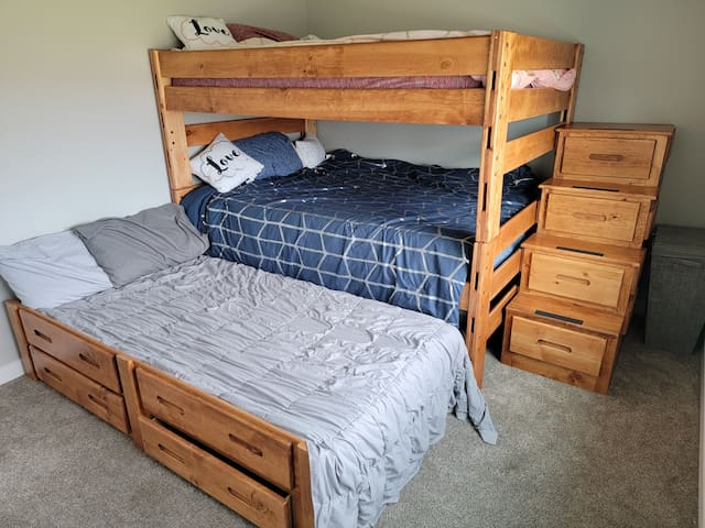 This bedroom includes full over full bunk beds with a pull out twin bed. There are 4 drawers for storage space in the stairs as well as 2 drawers on the pull out bed.