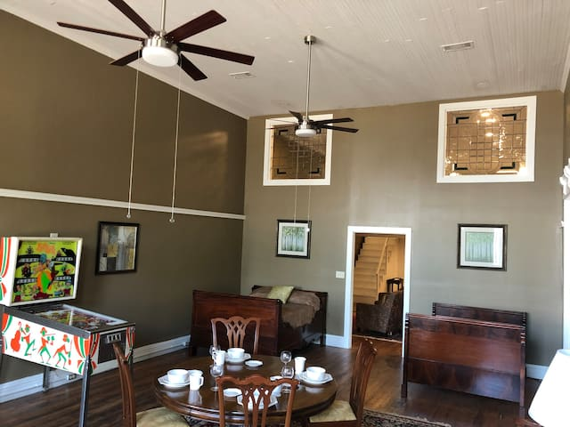 Front Room - 2 beds, dining table/conference table, pinball machine