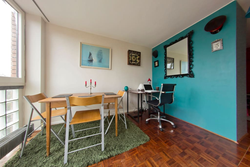 Dining area with desk which is partitioned from the bedroom area by a wardrobe