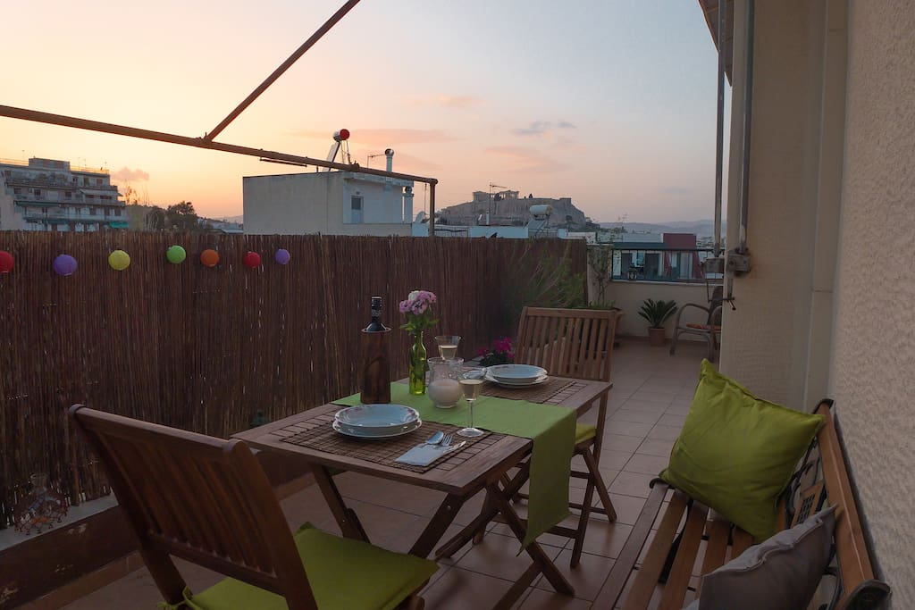 Large balcony with dinning table, bench, sunbed, parasol and magnificent view to the Acropolis.