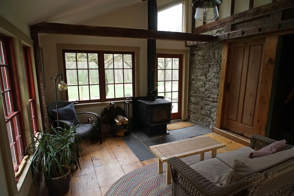 Sunroom off of the kitchen with wood stove. The French door leads to a trellised flagstone patio.