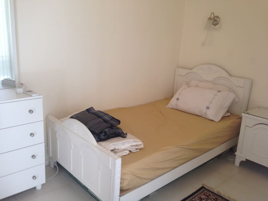 Large single bed in the bedroom, with hanging cupboard, chest of drawers, mirror and bedside table