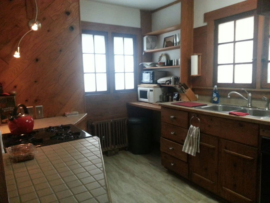 Big kitchen with high counter tops and a gas stove