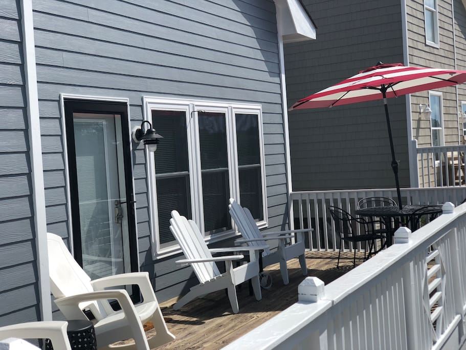 Deck facing the ocean with table, 4 chairs, 2 Adirondack chairs, 3 rocking chairs, tables.