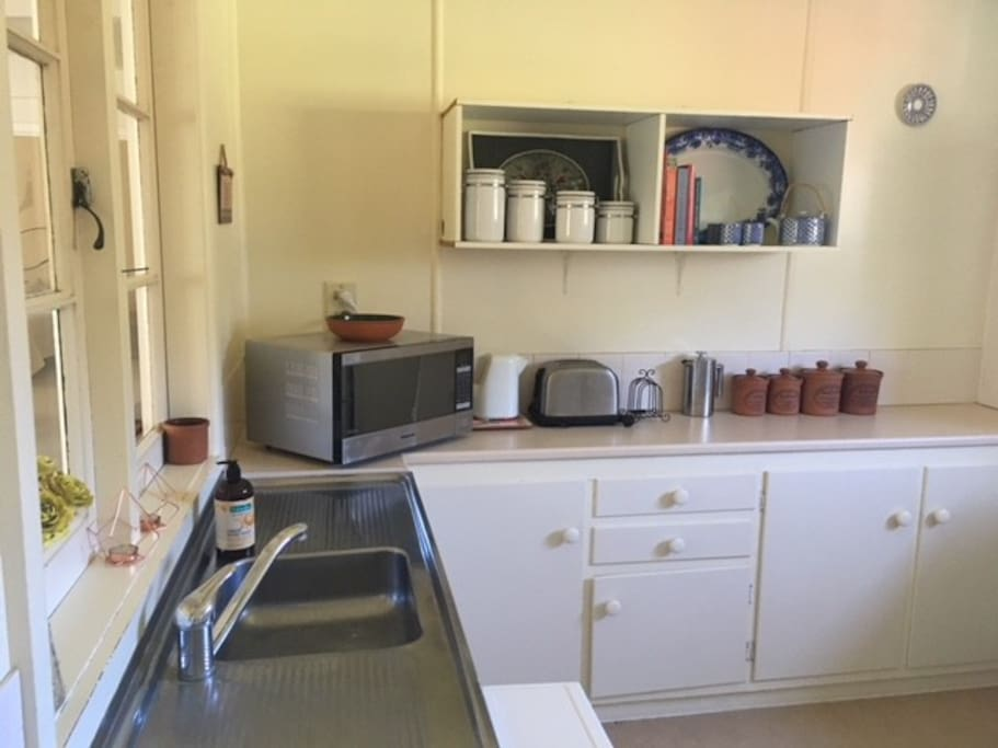 Kitchen- features fridge, microwave, stove, and oven, as well as cutlery and crockery