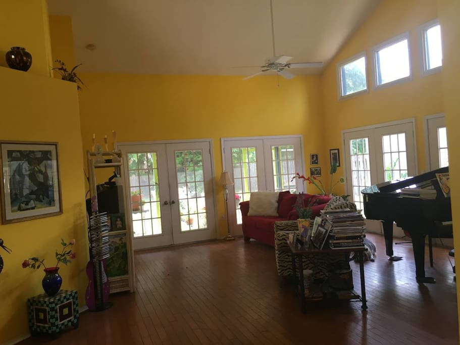 Living room, piano, doors leading to large private backyard.