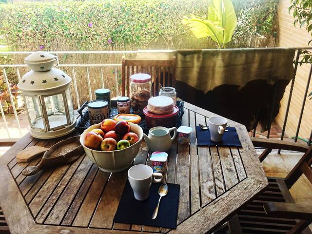 Desayuno en el porche del salón con vistas al jardín y la piscina