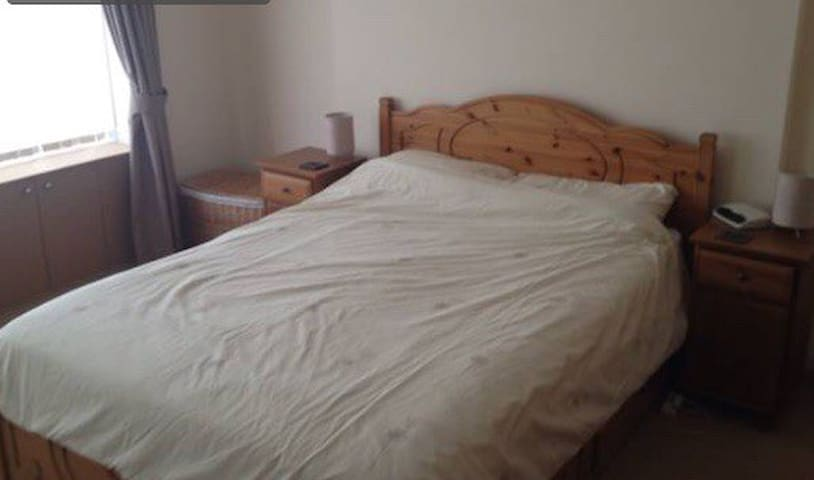 King size bedroom with chest of drawers and large wardrobe