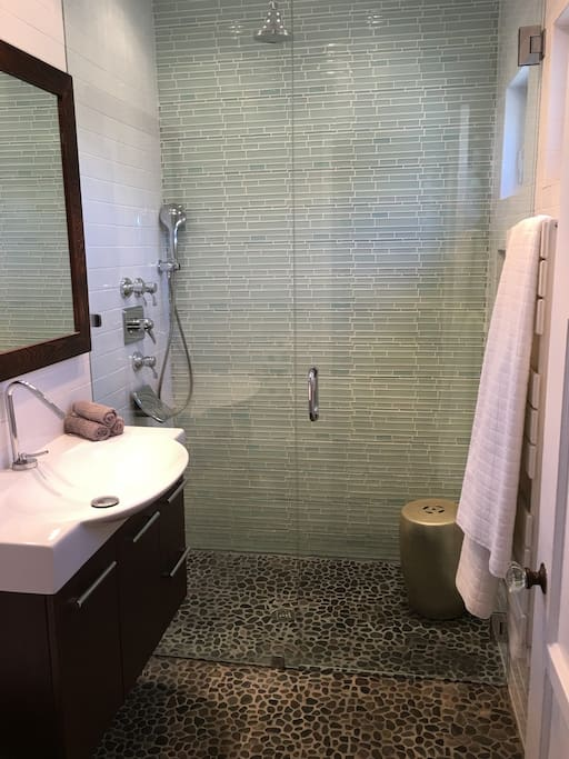 Spa-style bathroom-(tankless water heater, large shower stall with dual overhead and hand held shower heads).