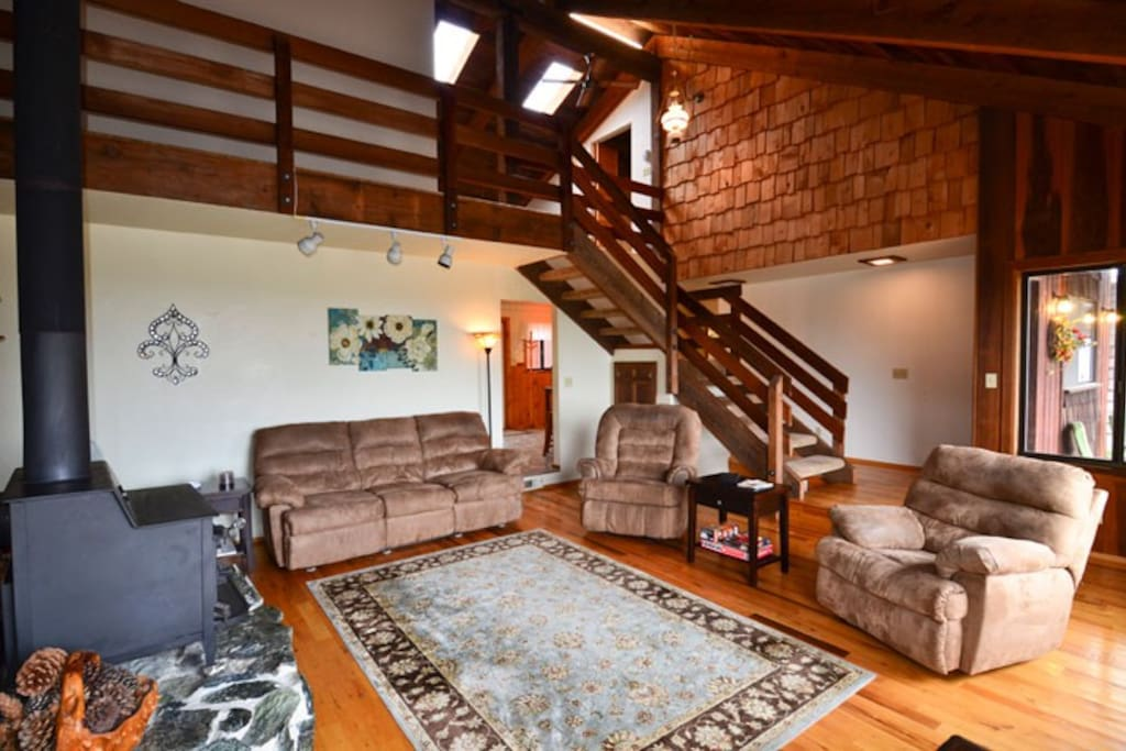 Large living room with comfortable seating and a woodstove and TV.