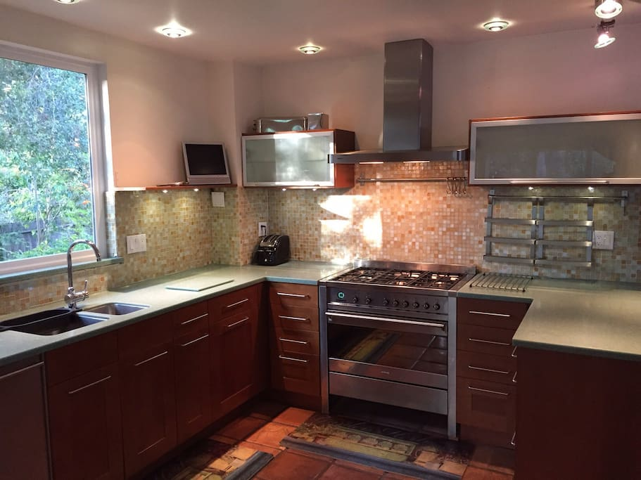 Kitchen with all stainless steel appliances and Smeg 6 burner gas stove