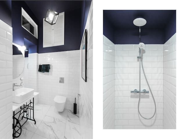 Uniquely designed bathroom features a walk-in shower. Original Yves Saint Laurent poster combined with early XX century Naumann sewing machine.