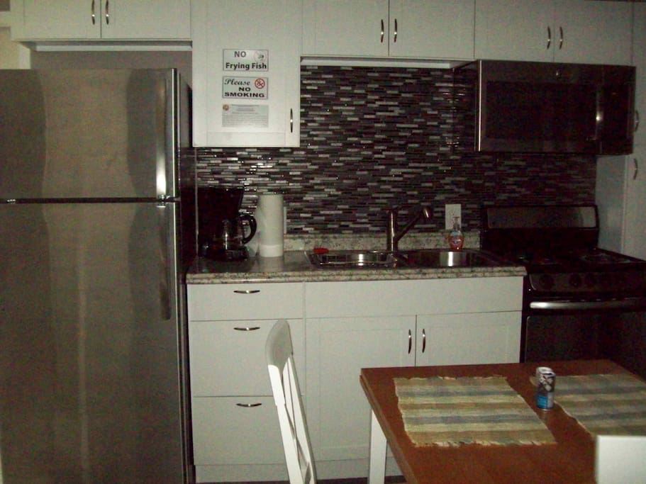 Full kitchen with microwave, coffee maker and full size refrigerator.