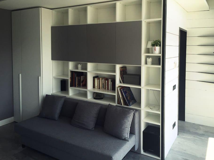 Parete attrezzata, libreria, colonna armadio, divano letto 1 piazza e mezzo. Ampie finestre terrazzo.