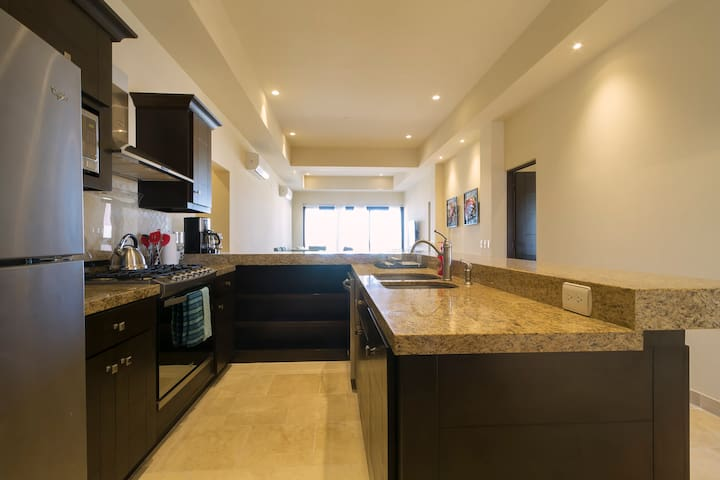 The kitchen is fully-loaded with high-end appliances including a gas stove, oven, full-sized refrigerator, tea kettle, coffee maker, blender & toaster.