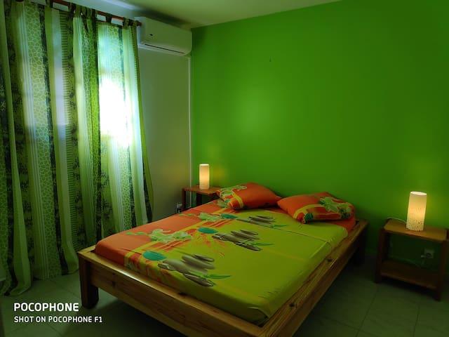 Chambre climatisée pour deux personnes avec un fauteuil, tables et lampes de chevet.
