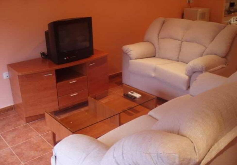 Salón con dos sofás y TV.