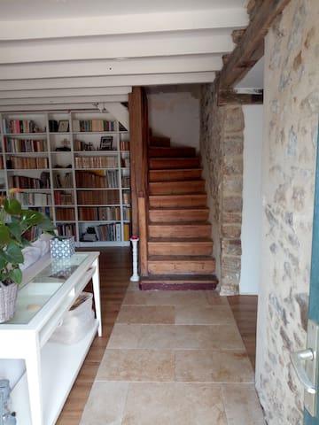 Entrée et escalier vers l'étage. A droite la cuisine/salle à manger, à gauche le salon