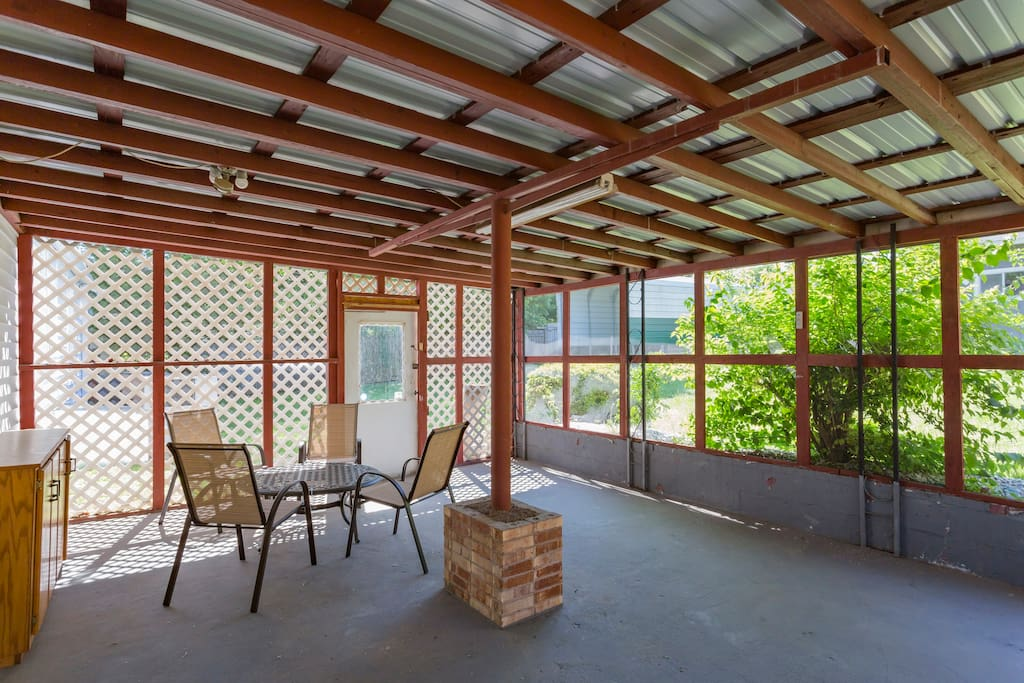Spacious, screened in patio space with chairs, table and bar! This is a popular area for coffee in the AM and adult beverages in the PM!