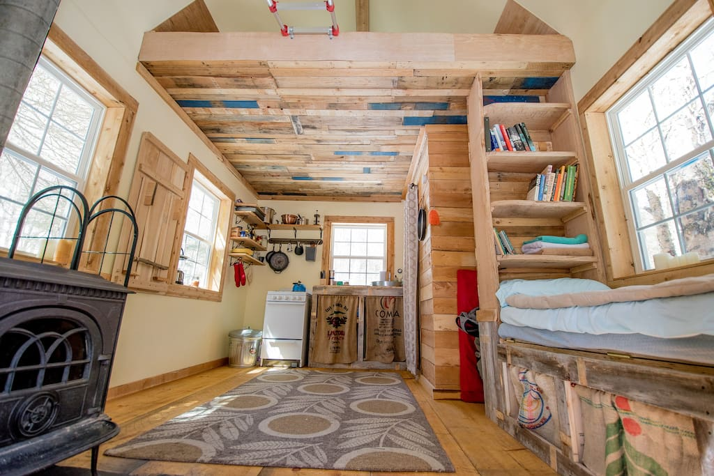 The inside of Alder Brook Cottage. Featuring a wood stove, kitchenette, bookshelves, fold-down table, daybed, bathroom, and a loft bedroom.