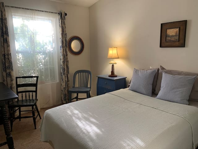 West room features a comfy bed, 3 pillows, a desk and chairs and a large closet for hanging clothes and shelving.