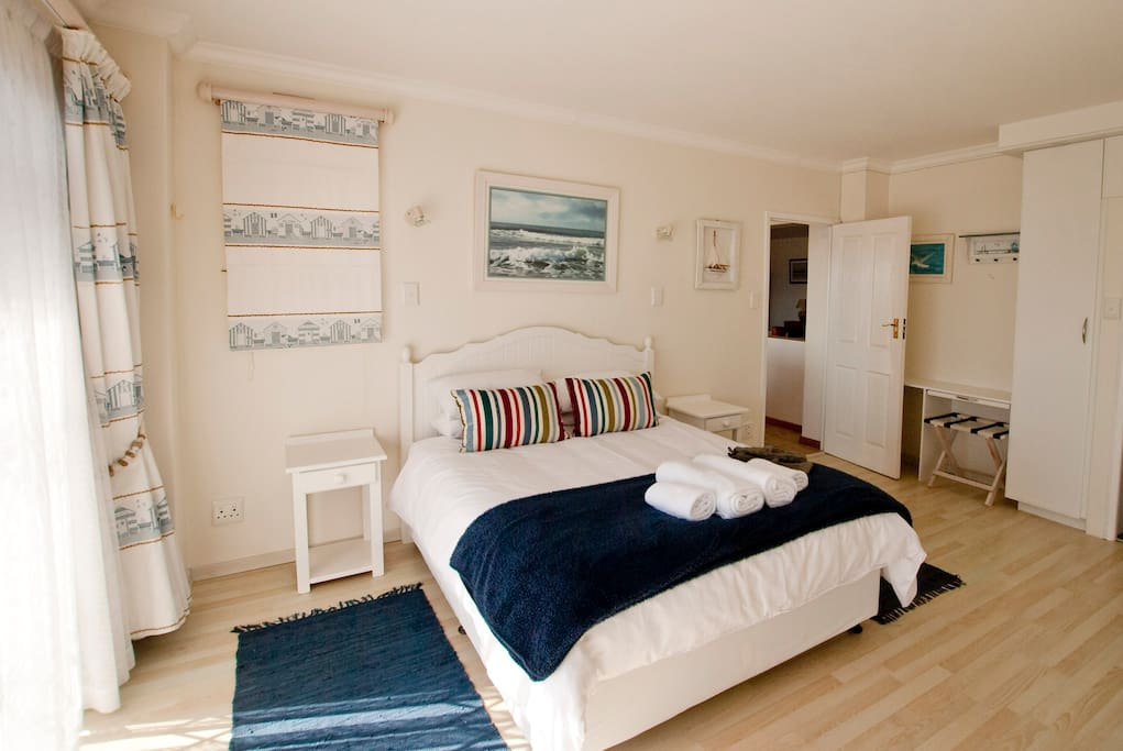 Main bedroom with double bed and en-suite bathroom with shower and bath.
