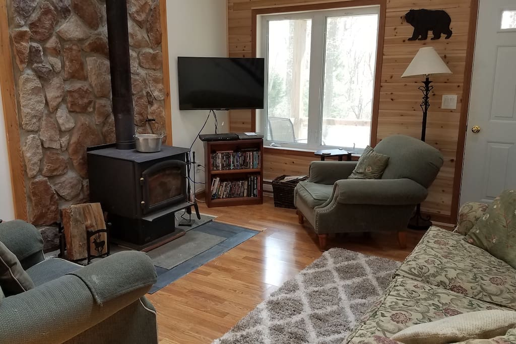 Living room has hardwood floor, full size couch, two chairs, firebox and TV with Dish Network and DVD
