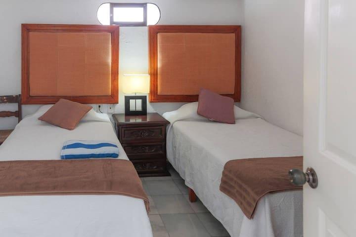 Recámara con dos camas individuales y baño completo.