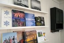 Interesting coffee table books are displayed on the wall.